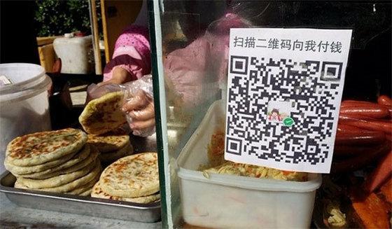 중국에선 모바일 페이가 대세다. 음식을 파는 중국의 노점상은 위생 문제를 이유로 현금 결제보다 위챗페이나 알리페이 같은 모바일 결제를 선호한다. [중앙포토]