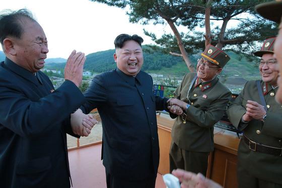 지난 14일중장거리탄도미사일(IRBM) '화성-12형'의 시험발사 현장을 참관한뒤 간부들과 파안대소하는 북한 김정은.[노동신문]