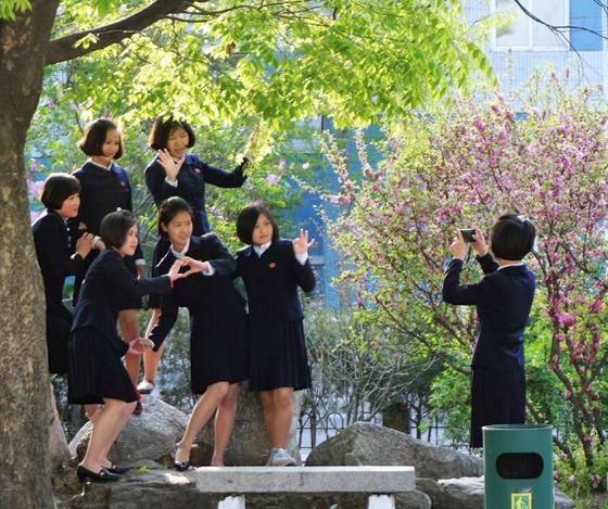평양 대동문 인근에서 핸드폰 사진을 찍고 있는 북한 여고생들. 손으로 하트모양을 만든 친구들을 핸드폰으로 찍는 학생의 모습이 진지해보인다.[Sejin Pak 페이스북]