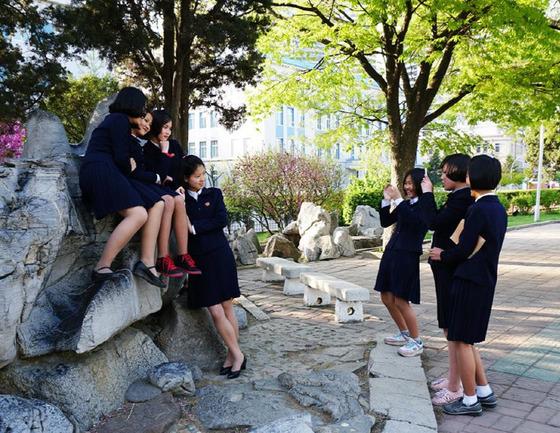 평양 대동문 인근에서 핸드폰 사진을 찍고 있는 북한 여고생들. 턱을 괴고 팔을 마주잡으며 포즈를 취한 친구를 보며 한 여학생이 박장대소하고 있다.[Sejin Pak 페이스북]