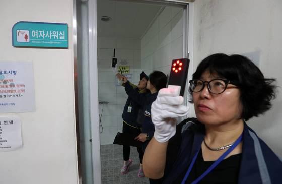 서울시 여성안심보안관 박광미(오른쪽)씨가 12일 서울 용산구 청파동 헬스장의 샤워실과 탈의실에서 적외선 탐지기의 불빛을 이용해 몰래 카메라를 탐지하고 있다. 김상선 기사