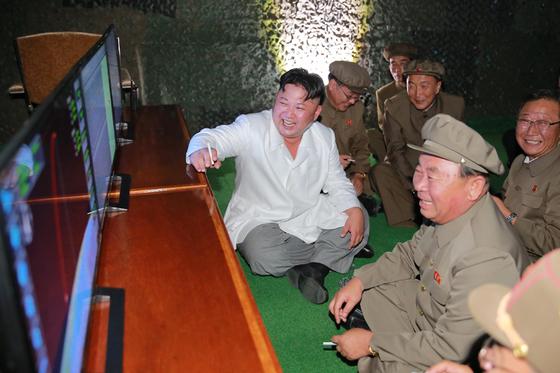 지난해 8월 SLBM 시험 발사 성공 장면을 지켜본 김정은이 미사일 개발을 주도한 이병철 당 제1부부장과 함께 맞담배를 피고 있다. [사진 노동신문]
