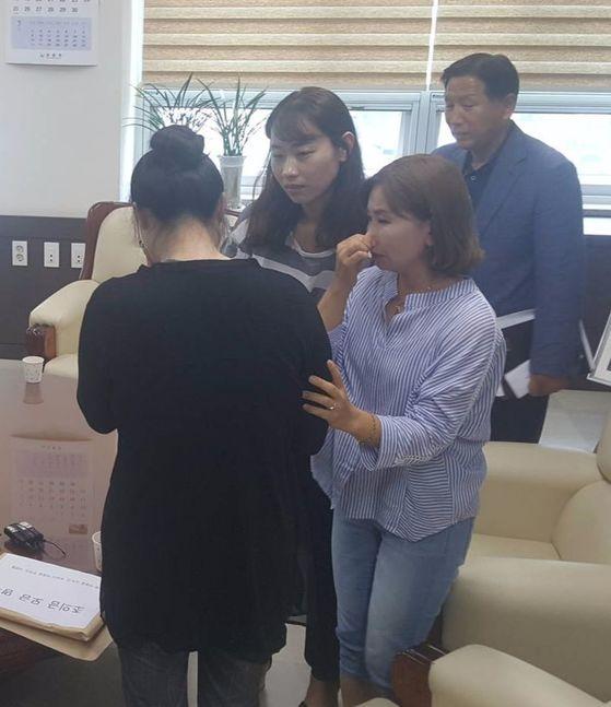 20일 경남 양산경찰서에서 시민들이 ' 밧줄 사건' 피해자의 부인(왼쪽)을 위로하고 있다. [위성욱 기자]
