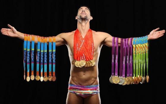 """미국의 스포츠일러스트레이티드(SI)가 이제까지 4차례 올림픽(2004·08·12·16년)에서 따낸 28개 메달(금23·은3·동2)을 몸에 건 '수영 황제' 마이클 펠프스(미국)의 화보 사진을 21일 공개했다. 펠프스는 """"무거워서 거절했지만 결국 메달을 다 챙겨왔다""""고 말했다.  [사진제공=SI 인스타그램]"""