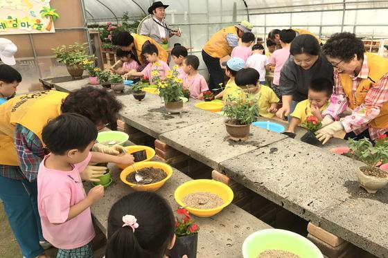 화분체험에서 아이들이 진행자인 할머니·할아버지와 함께 꽃을 심고 있다. [사진 효령노인복지타운]