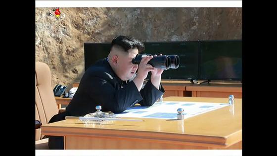 김정은 북한 노동당 위원장이 4일 평북 방현일대에서 진행한 대륙간탄도미사일 화성-14의 발사장면을 쌍안경으로 보고 있다. [사진=조선중앙TV 촬영]