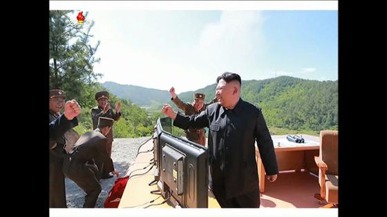 김정은 북한 노동당 위원장이 4일 대륙간탄도미사일(ICBM) 화성-14 발사 직후 관계자에게 손을 흔들고 있다. [사진=조선중앙TV 캡쳐]