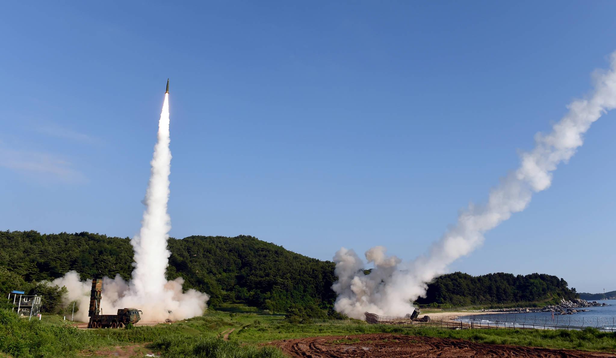 북한의 대륙간탄도미사일(ICBM) 도발에 대응해 5일 오전 동해안에서 열린 한미 연합 탄도미사일 타격훈련에서 한국군 탄도미사일 현무-2A(왼쪽)와 주한미군 에이태킴스(ATACMS)가 동시 발사되고 있다. [합동참모본부=연합뉴스]