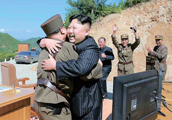 북한 김정은 노동당 위원장이 지난 4일 대륙간탄도미사일(ICBM) '화성-14형' 발사에 성공한 뒤 군 지휘부와 기뻐하고 있다. [노동신문=연합뉴스]