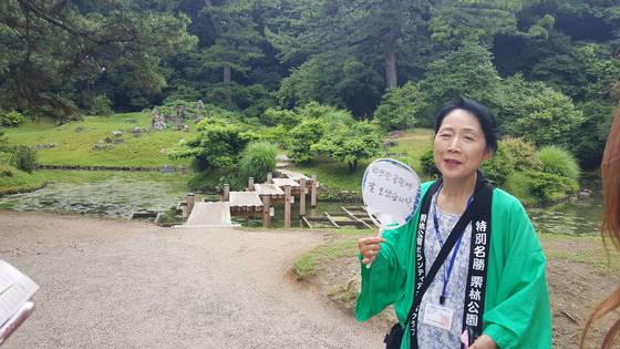 '리쓰린 공원에 잘 오셨습니다'란 문구를 쓴 부채를 든 한국어 자원봉사자. 한국어가 조금 서툴긴 했지만 한국에 대한 애정으로 한국에서 온 손님들을 맞았다.