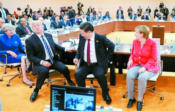 지난 7일 독일 함부르크에서 열린 주요 20개국(G20) 정상회의 실무회의에서 특유의 표정과 자세를 취하고 있는 도널드 트럼프 미국 대통령을 시진핑 중국 국가주석, 앙겔라 메르켈 독일 총리가 웃으며 바라보고 있다(왼쪽부터). 트럼프 뒤쪽으로 문재인 대통령이 아베 신조 일본 총리와 나란히 앉은 모습이 보인다. [AFP=연합뉴스]