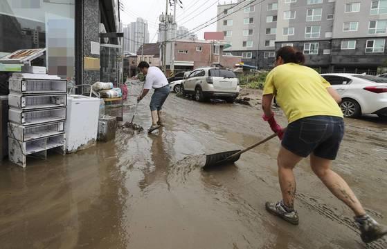 지난 16일 오후 청주시 흥덕구 폭우 침수 지역 주택가에서 시민들이 힘을 모아 진흙을 치우고 있다. [연합뉴스]
