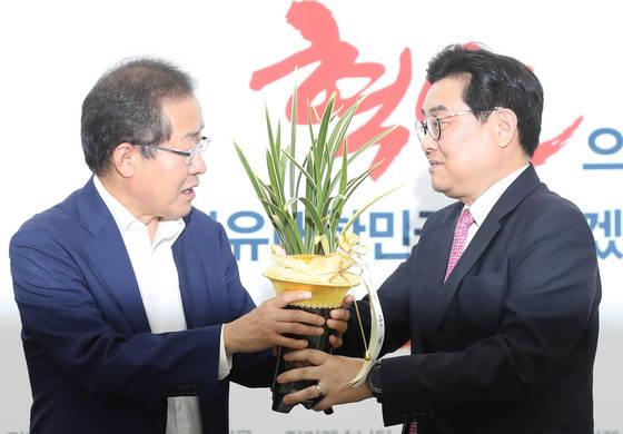 자유한국당 홍준표 대표(왼쪽)가 지난 4일 국회 대표실을 예방한 전병헌 정무수석으로부터 문재인 대통령 축하난을 받고 있다.