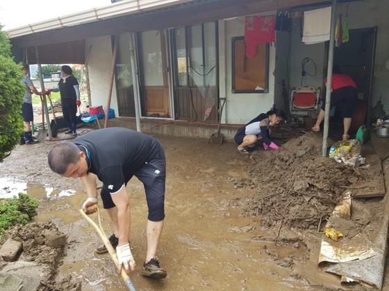 16일 오전 충북 청주시 월오동 주민들이 집안에 쌓인 흙과 물을 빼내고 있다. 최종권 기자
