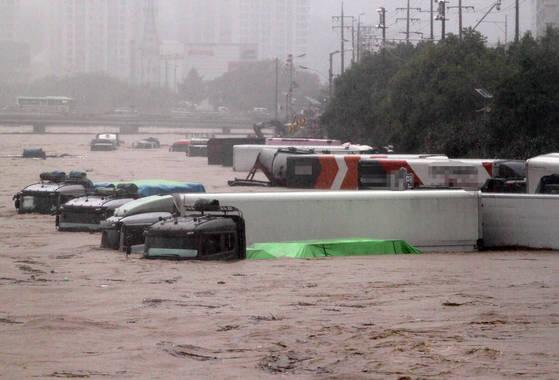 지난 16일 쏟아진 폭우로 충북 증평 보강천 하상 주차장이 물에 잠겼다. 주차 차량이 모두 침수돼 있다. [연합뉴스]
