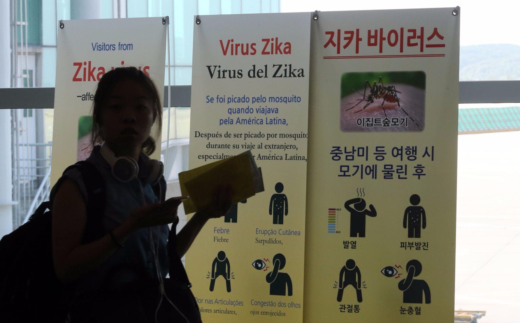인천국제공항으로 입국한 해외 여행객이 지카 바이러스 안내문을 읽고 있다. 여름 휴가철을 맞아 외국으로 나가는 여행객들은 지카 등 감염병에 걸리지 않도록 예방하는 게 중요하다. [중앙포토]