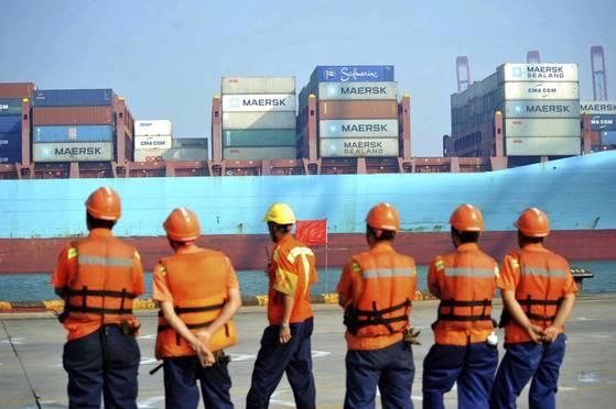 중국 2분기 성장률 6.9%를 이끈 요소는 무역이었다. 중국 산둥성 칭다오 항구에서 근로자들이 컨테이너 화물선이 입항하는 것을 지켜보고 있다. [칭다오 AP=연합뉴스]
