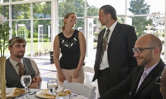 사라 커민스가 15일(현지시간) 자신의 결혼식 디너 연회에 초대한 노숙인들과 웃으며 이야기를 나누고 있다. [가디언 캡처]