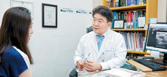 강남차병원 외과 박해린 교수가 유방 초음파검사를 받은 30대 여성에게 유방 종양 제거 기구(맘모톰 프루브)를 보여주며 수술법을 설명하고 있다.