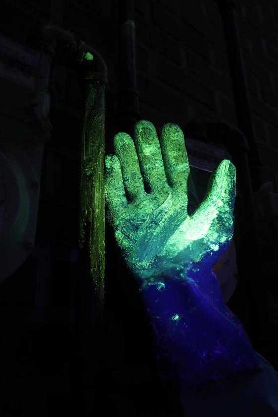 형광물질이 묻은 장갑도 특수조명을 받자 빛을 내고 있다.[김경록 기자]