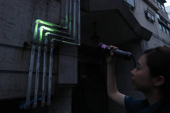 경찰관이 특수조명을 비추자 형광물질이 묻은 가스관이 빛을 발산하고 있다.[김경록 기자]
