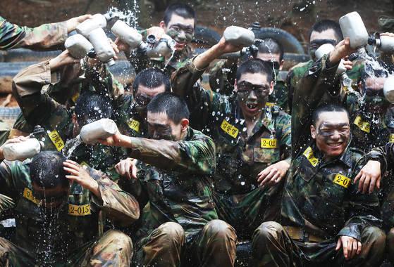 폭염이 계속되고 있는 19일 오전 경기도 용인시 육군 55사단 신병교육대에서 각개전투 훈련을 마친 훈련병들이 수통의 물을 서로에게 뿌려주며 더위를 식히고 있다. [연합뉴스]