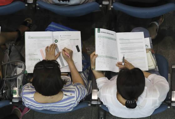 학부모들이 22일 오후 이화여대 대강당에서 수시모집 지원전략 설명을 메모하고 있다. 임현동 기자