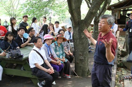 지난 22일 밀양꽃새미마을의 팜스테이를 이끌고 있는 참샘허브나라 손정태(57) 대표가 마을을 찾은 관광객들에게 마을 소개를 하고 있다. 위성욱 기자