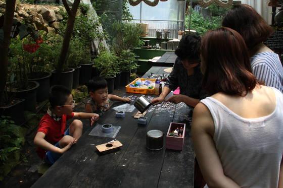 지난 21일 밀양꽃새미마을 참샘허브나라에서 관광객들이 허브양초만들기 체험을 하고 있다. 위성욱 기자