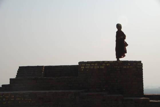 인도의 불교 유적지에 있는 탑 위에 한 동자승이 서 있었다. 그는 무엇을 찾고 있는 걸까.