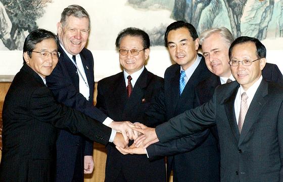 북핵 문제를 다루기 위한 제1차 6자회담이 2003년 8월 중국 베이징에서 열렸다. 각국 대표가 회의 시작에 앞서 손을 맞잡고 있다. 왼쪽부터 야부나카 미토지 일본 외무성 아시아·태평양국장, 제임스 켈리 미국 국무부 동아태담당 차관보, 김영일 북한 외무성 부상, 왕이 중국 외교부 부부장, 알렉산드로 로슈코프 러시아 외무차관, 이수혁 외교통상부 차관보. [베이징=연합뉴스]