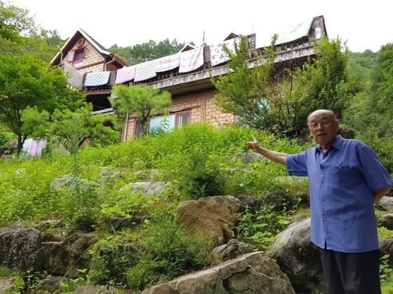 충북 제천시 봉양읍 묘재마을 주민 박운서씨가 지난 7월 27일 오후 누드동호회 회원들이 휴양시설로 쓰는 펜션을 가르키고 있다. 최종권 기자