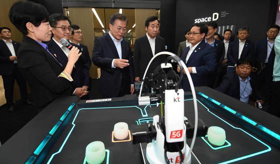 문재인 대통령이 17일 오후 서울 강서구 마곡 R&D 단지에서 열린 혁신성장 보고대회에서 KT관계자로부터 5G를 이용한 동작인식 설명을 들으며 체험해보고 있다. 청와대사진기자단