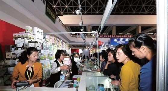 지난해 평양 봄철국제상품전람회장을 둘러보며 상품을 구입하는 평양 시민들.