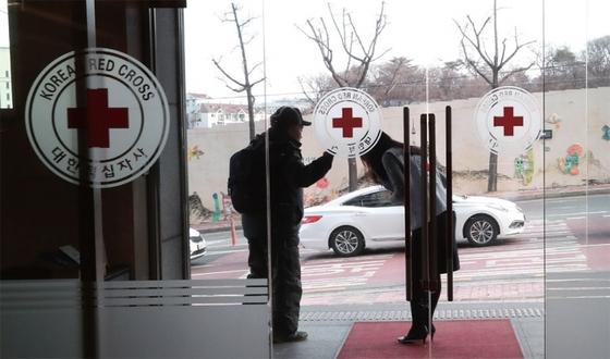 이산가족인 김영식 할아버지가 1월 9일 서울 중구 대한적십자사 본사를 찾아 이산가족 상봉 신청서를 작성한 뒤 직원의 배웅을 받고 있다.