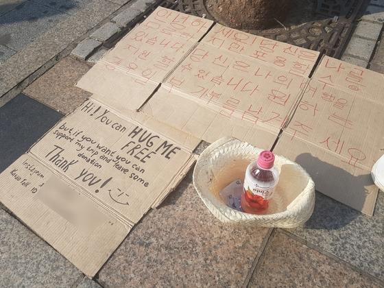 홍대입구에서 프리허그를 하는 베그패커들이 기부를 요청하는 문구. 김지아 기자