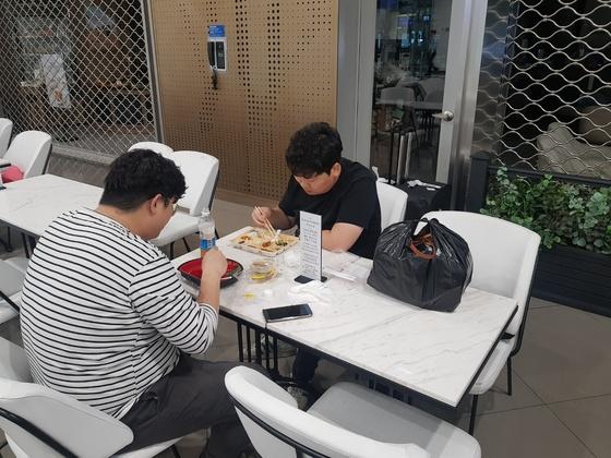 늦은 밤 인천공항 2터미널 지하1층 식당가에서 두 청년이 편의점 도시락을 먹고 있다. 함종선 기자