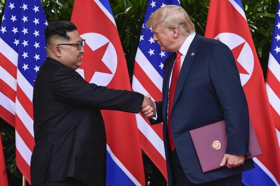 도널드 트럼프 미국 대통령과 김정은 북한 국무위원장이 12일 싱가포르 카펠라 호텔에서 서명식을 끝낸 뒤 악수하고 있다. [AP=연합뉴스]