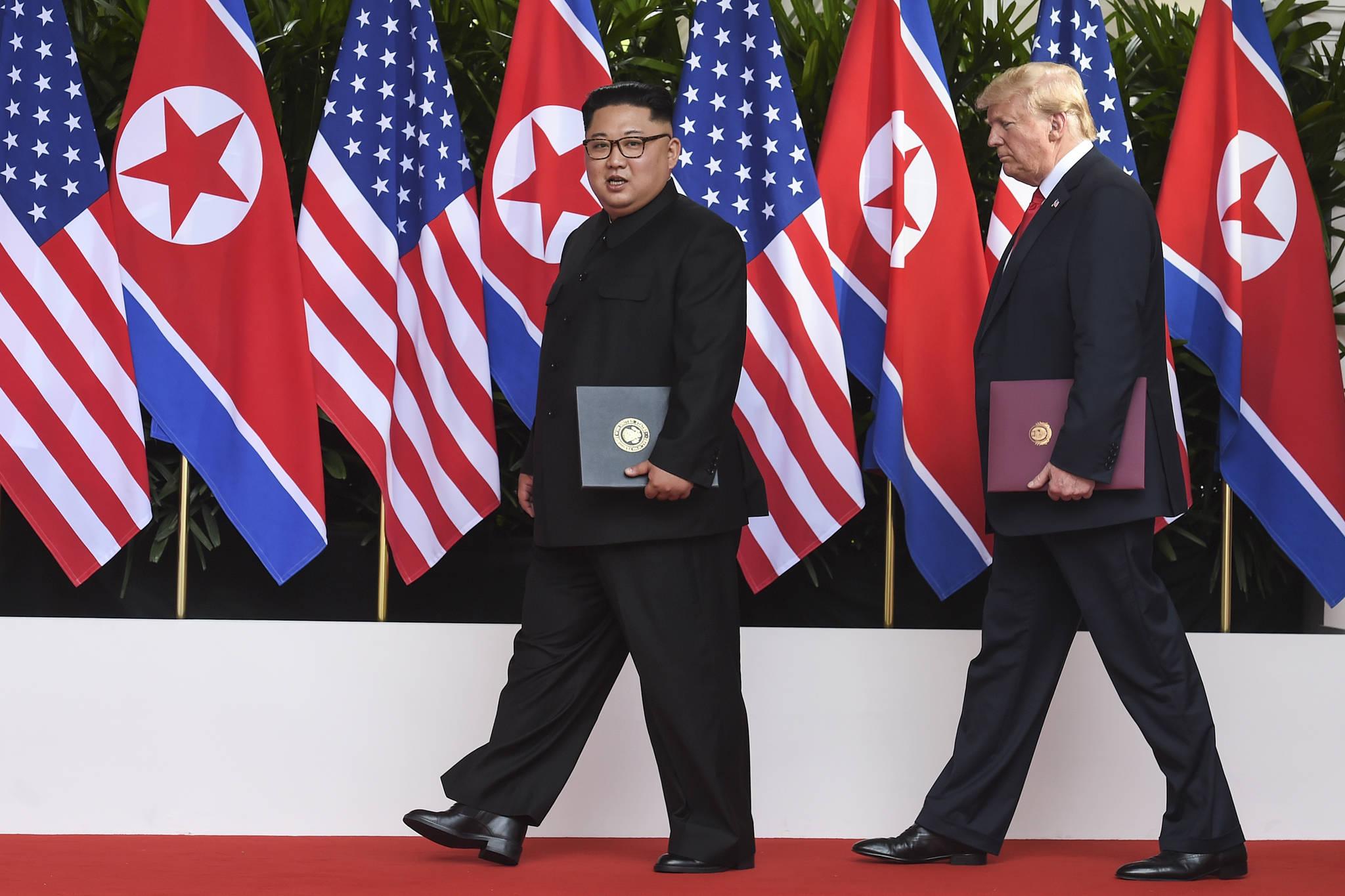 김정은 북한 국무위원장과 도널드 트럼프 미국 대통령이 합의문을 들고 화랑을 빠져나가고 있다. 나란히 걷는 양 정상의 키가 엇비슷하다. [AP=연합뉴스]