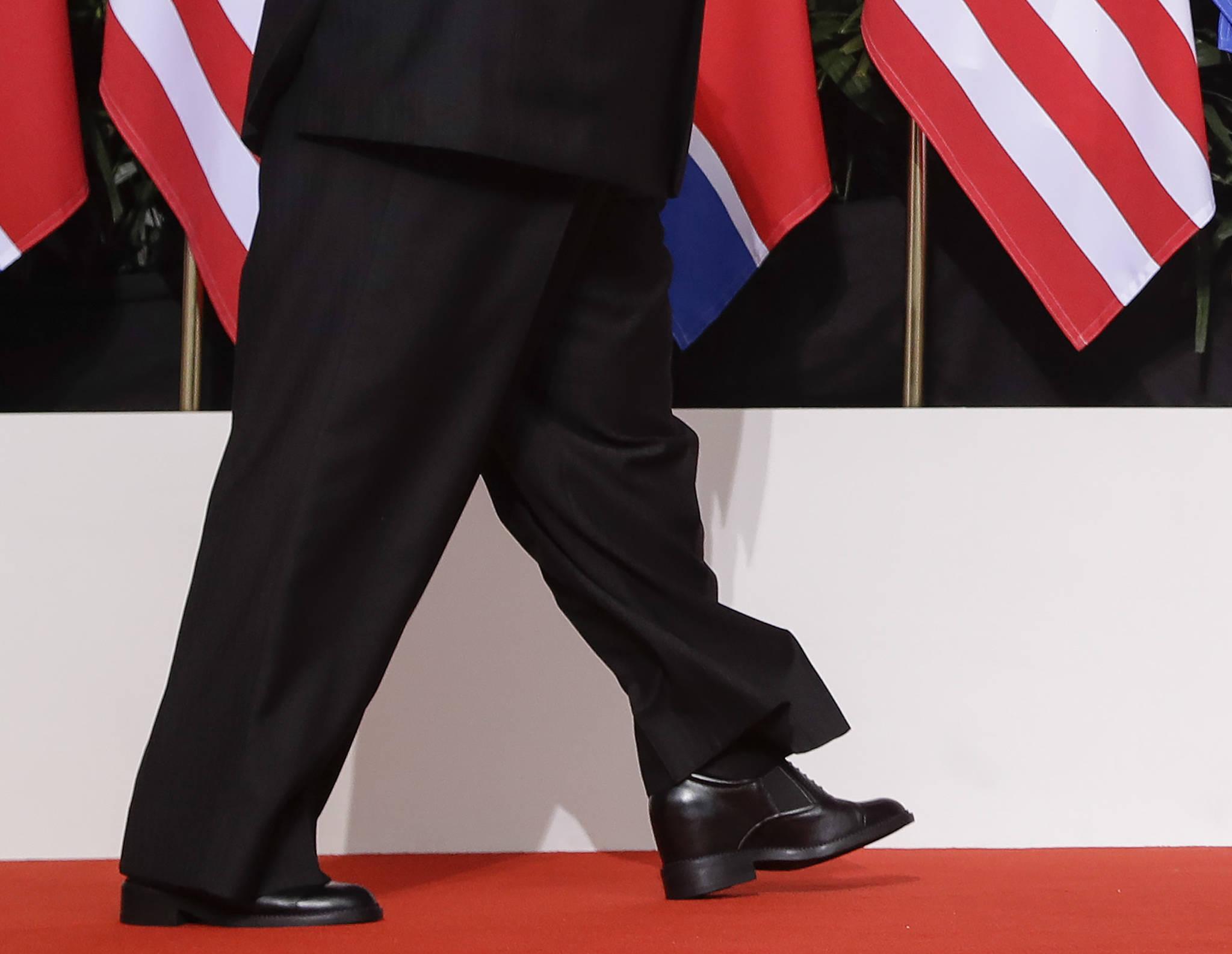 김정은 북한 국무위원장이 12일(현지시간) 싱가포르 센토사 섬의 카펠라 호텔에서 북·미 정상회담 합의문 서명식을 마치고 도널드 트럼프 미국 대통령과 악수하기 위해 걸어가고 있다. 이떄 김정은 위원장이 입은 통이 넓은 인민복 바지에 가려 보이지 않던 굽이 높은 구두가 이동 중 바지가 치켜올라가 드러났다. [AP=연합뉴스]
