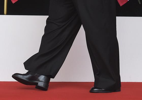 김정은 위원장이 굽을 높은 구두를 신고 걷고 있다. [AP=연합뉴스]