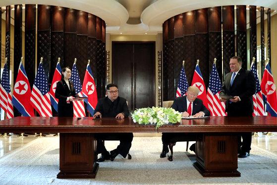 도널드 트럼프 미국 대통령과 김정은 북한 국무위원장이 12일 싱가포르 카펠라 호텔에서 공동성명에 서명하고 있다. [로이터=연합뉴스]