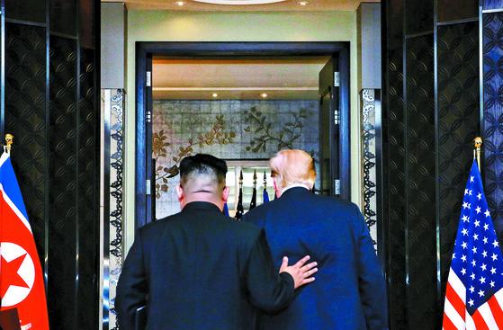 김정은 북한 국무위원장(왼쪽)과 도널드 트럼프 미국 대통령이 12일(현지시간) 싱가포르의 카펠라 호텔에서 북·미 정상회담 공동성명 문서에 서명을 마치고 이동하고 있다. [신화=연합뉴스]