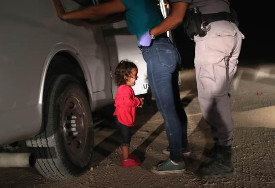 엄마와 함께 뗏목을 타고 리오그란데 강을 건너 미국-멕시코 국경지대에 있는 텍사스 주 매캘런에 도착한 두 살짜리 온두라스 여자 아이가 12일(현지시간) 엄마가 미국 국경순찰대로부터 몸수색을 받고 구금되자 울음을 터뜨리고 있다. [게티이미지=연합뉴스]