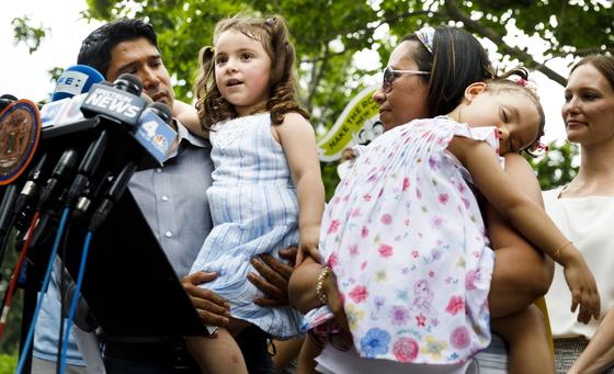 에콰도르 출신 이민자 파블로 비야비센시오의 딸 루치아나가 18일(현지시간) 미국 뉴욕 연방정부사무소 건물 앞에서 열린 '비야비센시오 석방 촉구 기자회견'에서 이야기하고 있다. 동생 안토니아가 엄마 샌드라 치카의 품에서 잠들어 있다. [EPA=연합뉴스]
