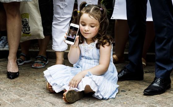 에콰도르 출신 이민자 파블로 비야비센시오의 딸 루치아나가 18일(현지시간) 미국 뉴욕 연방정부사무소 건물 앞에서 열린 '비야비센시오 석방 촉구 기자회견'에서 핸드폰 속 아빠 사진을 보여주고 있다. [EPA=연합뉴스]
