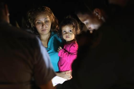 12일(현지시간) 뗏목을 타고 리오그란데 강을 건너 미국-멕시코 국경지대에 있는 텍사스 주 매캘런에 도착한 두 살짜리 온두라스 여자 아이와 엄마가 미국 국경 순찰대에 체포돼 이동하고 있다.[게티이미지=연합뉴스]