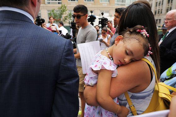 18일(현지시간) 미국 뉴욕 연방정부사무소 건물 앞에서 열린 '에콰도르 출신 이민자 파블로 비야비센시오 석방 촉구 기자회견'에서 비야비센시오의 막내 딸 안토니아가 엄마 품에 잠들어 있다. [EPA=연합뉴스]
