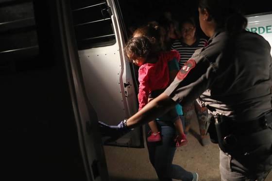 12일(현지시간)뗏목을 타고 리오그란데 강을 건너 미국-멕시코 국경지대에 있는 텍사스 주 매캘런에 도착한 두 살짜리 온두라스 여자 아이와 엄마가 체포돼 미국 국경순찰대 차량에 탑승하고 있다.[게티이미지=연합뉴스]
