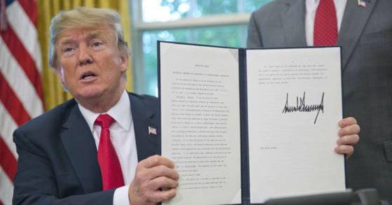 도널드 트럼프 미국 대통령은 20일(현지시간) 워싱턴 백악관 집무실에서 밀입국 이민가족 격리 조치를 종료하는 행정명령에 서명했다. [AP=연합뉴스]